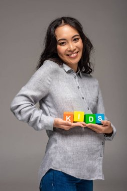 pregnant young asian woman holding alphabet cubes with word kids isolated on grey