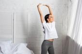 Asijské žena v bílé tričko a šedé leginy dělá protahovací cvičení s rukou