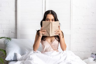 beautiful asian woman in elegant nighty with obscured face sitting in bed
