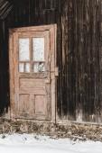 Fotografie old weathered wooden house with door in winter