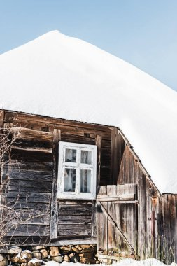 old wooden house covered with snow in winter