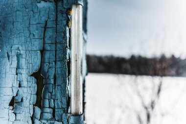 selective focus of thermometer in weathered old blue board in winter