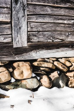 pile of rocks under aged wooden house with sunlight