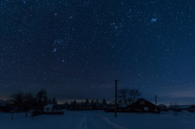 starry night sky above village covered with snow in carpathian mountains
