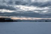 Landschaft der Karpaten bedeckt im Morgengrauen mit Schnee mit bewölktem Himmel und Bäume.