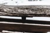 Selektivní fokus věku zvětralé rustikální dřevěné prkno na zasněžené pozadí