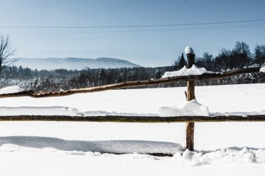wooden fence covered with snow in carpathian mountains