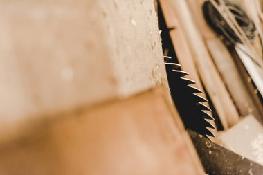 selective focus of round metal saw disc cutting wooden plank