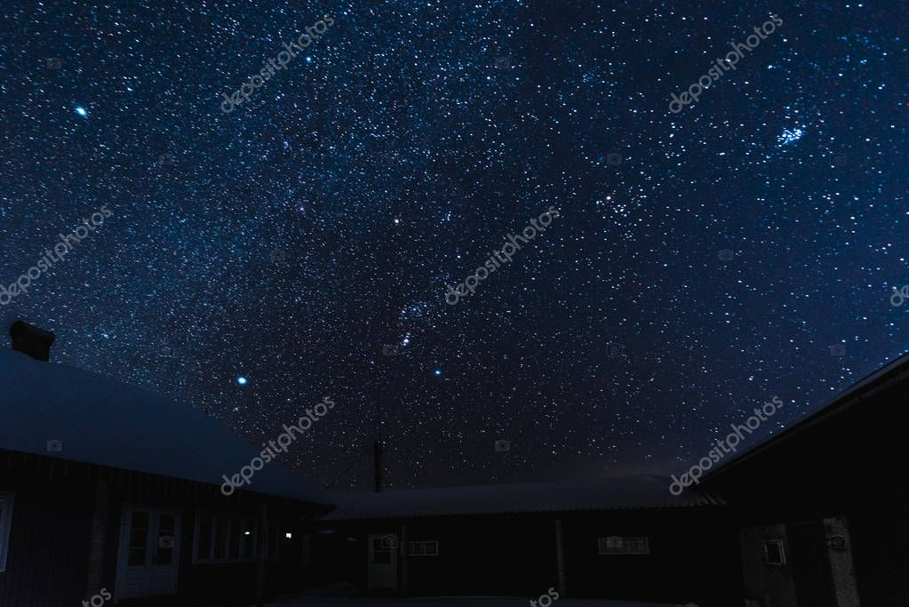 starry dark sky and houses covered with snow at night in winter
