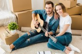 Photo Smiling man sitting on carpet with wife and playing acoustic guitar