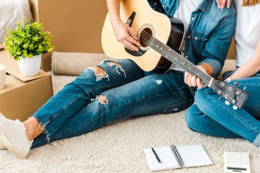 Cropped view of man sitting on carpet with wife and playing acoustic guitar