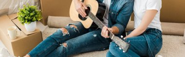 Panoramic shot of man sitting on carpet with wife and playing acoustic guitar