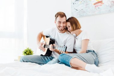 Smiling man sitting on bed with wife and playing guitar