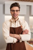 Fotografie Smiling barista in glasses and brown apron looking at camera with crossed arms