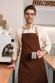 Fotografie Lächelnder Barista in Gläsern und brauner Schürze mit Milchkanne im Café