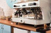 Modern coffee machine on wooden surface in cafe