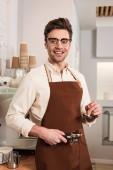 Fotografie Lächelnder Barista in Gläsern und brauner Schürze hält Portafilter mit gemahlenem Kaffee und Manipulation