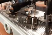 Selektivní zaměření kávovaru a dvou nerezových šálků