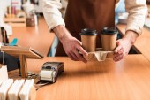 Ausgeschnittene Ansicht von Barista in brauner Schürze mit Kaffeebecher