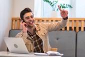 Fotografia Allegro libero professionista in giacca parlare su smartphone e mostrando idea segno in caffè