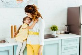 happy mother laughing and hugging with daughter together in kitchen