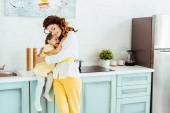 šťastná matka objímající roztomilou dceru v kuchyni