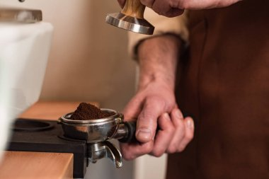 Cropped view of barista in brown apron preparing coffee