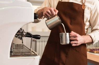 Cropped view of barista in brown apron pouring milk in steel cup