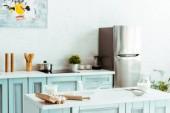 moderní lehká kuchyně s pekařskými složkami a kuchyňskými náčiní na stole