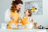 happy mother with excited daughter cooking dough together in kitchen