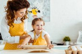 happy daughter in yellow polka dot apron rolling out dough on baking parchment paper next to mother