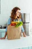 usměvavá žena stojící u papírového pytlíku s zralými plody a zeleninou v kuchyni