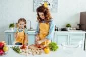 matka v Polce tečka zástěra řezání syrové zeleniny blízko dcery v kuchyni