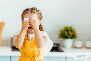 funny kid in yellow polka dot apron holding eggs in front of eyes in kitchen