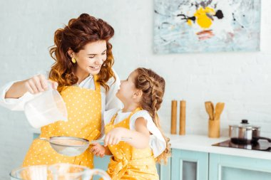 Selective focus of happy mother and daughter sieving flour together in kitchen stock vector