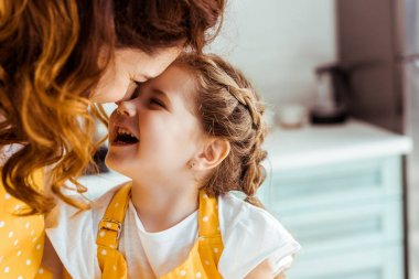 happy mother and cute daughter laughing together