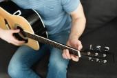 kivágott view zenész játszik akusztikus gitár otthon