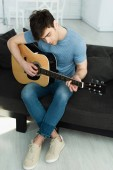 handsome musician playing acoustic guitar while sitting with crossed legs on sofa