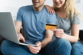 cropped view of blonde woman holding credit card near cheerful man using laptop