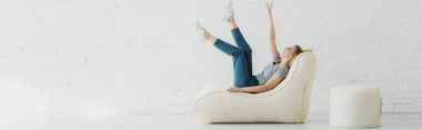 panoramic shot of cheerful blonde girl lying on  bean bag chair and gesturing near brick wall