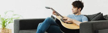 panoramic shot of handsome man sitting on sofa and playing acoustic guitar at home