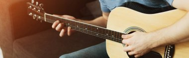 panoramic shot of musician playing acoustic guitar at home