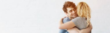 panoramic shot of happy man smiling while hugging blonde girl
