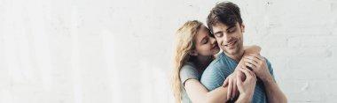 Panoramic shot of blonde cheerful girl hugging handsome and happy boyfriend stock vector