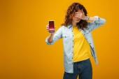 červená žena zakrývající oči a držící smartphone s obchodními kurzy na obrazovce oranžově