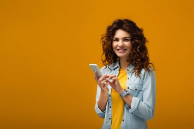 happy curly redhead woman holding smartphone on orange