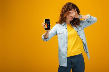 redhead woman covering eyes and holding smartphone with charts and graphs on screen on orange