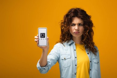 Upset redhead woman holding smartphone with uber app on screen on orange stock vector