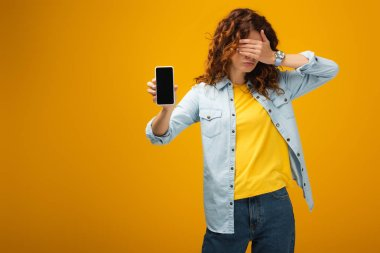 redhead woman covering eyes and holding smartphone with blank screen on orange