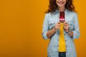 Fotografie oříznutý pohled na veselou kudrnaté ženu držící smartphone s obchodními kurzy na obrazovce oranžově